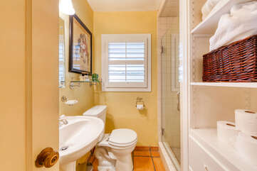 Saltillo tile floor gives character to second bath, with shower, pedestal sink, plenty of storage
