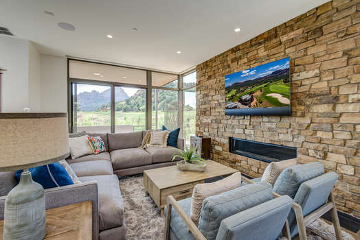 Contemporary Furnishings Surrounding a Gas Fireplace Amongst a Floor-to-Ceiling Stone Wall and 65