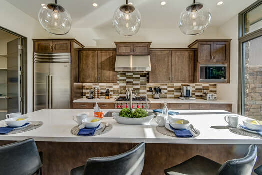 SubZero Stainless Steel Refrigerator and Large Quartz Island with Seating for Four