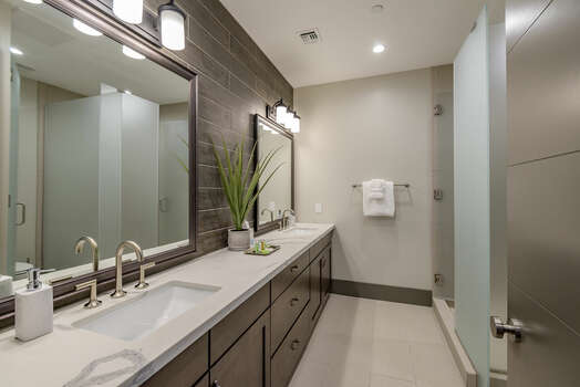 Full Shared Bath with Dual Quartz Countertop Sinks and Tile Shower