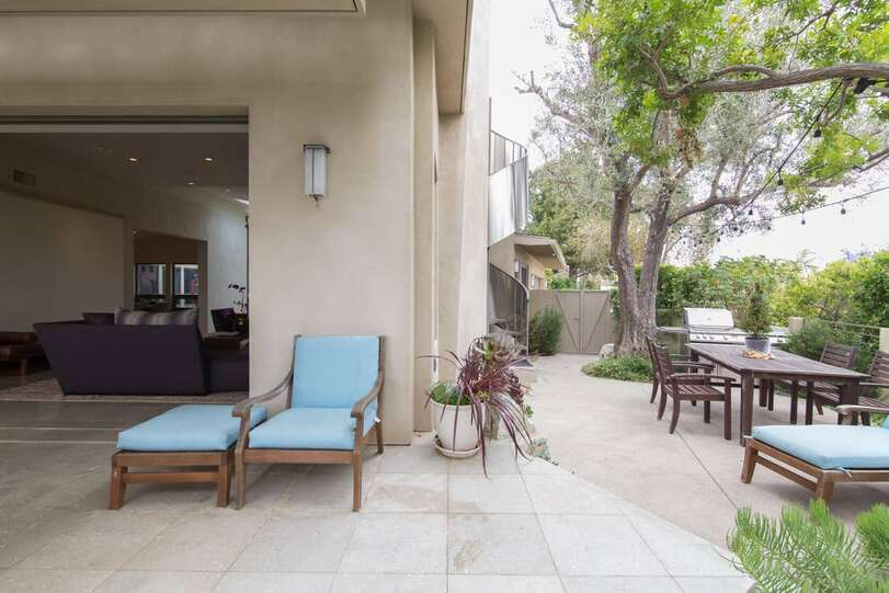 Side yard patio featuring gas barbecue and seating table to enjoy an outdoor meal.