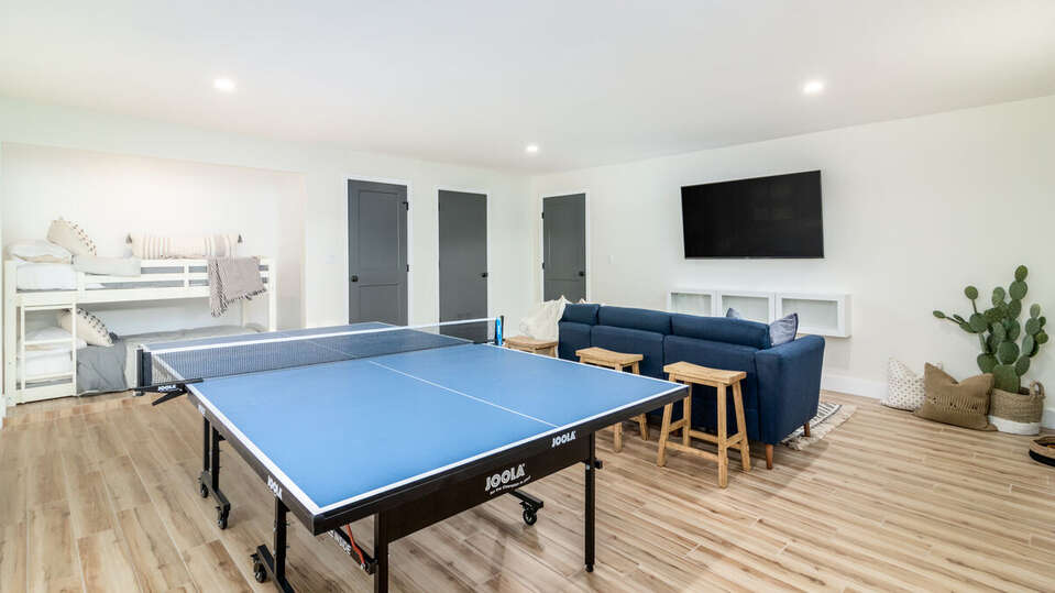 The Game Room with a second seating area that has HDTV and Bunk Beds and obviously a ping pong table!