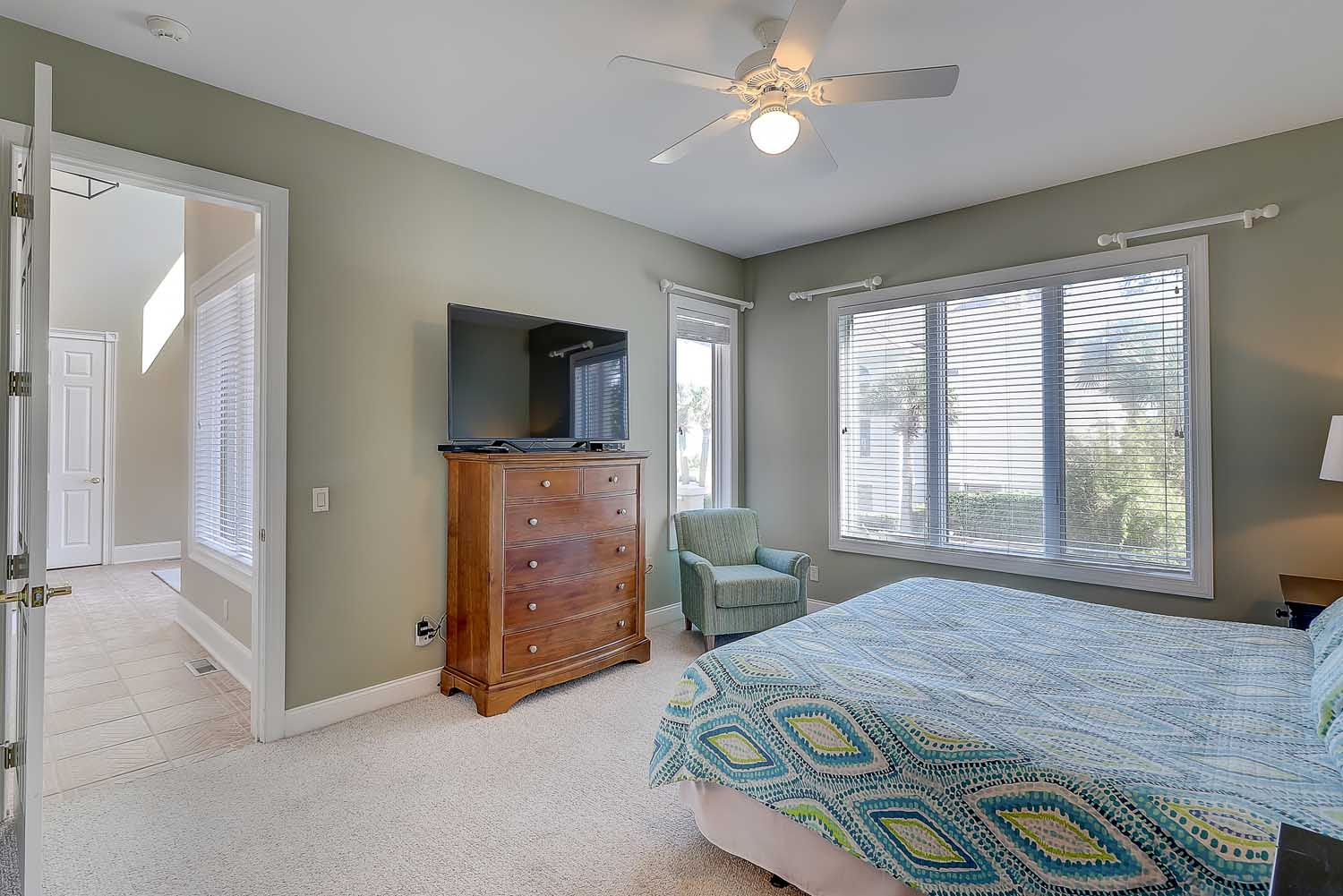 First floor king guest room has king bed, flat panel TV and en suite bathroom with dual vanities and walk in shower
