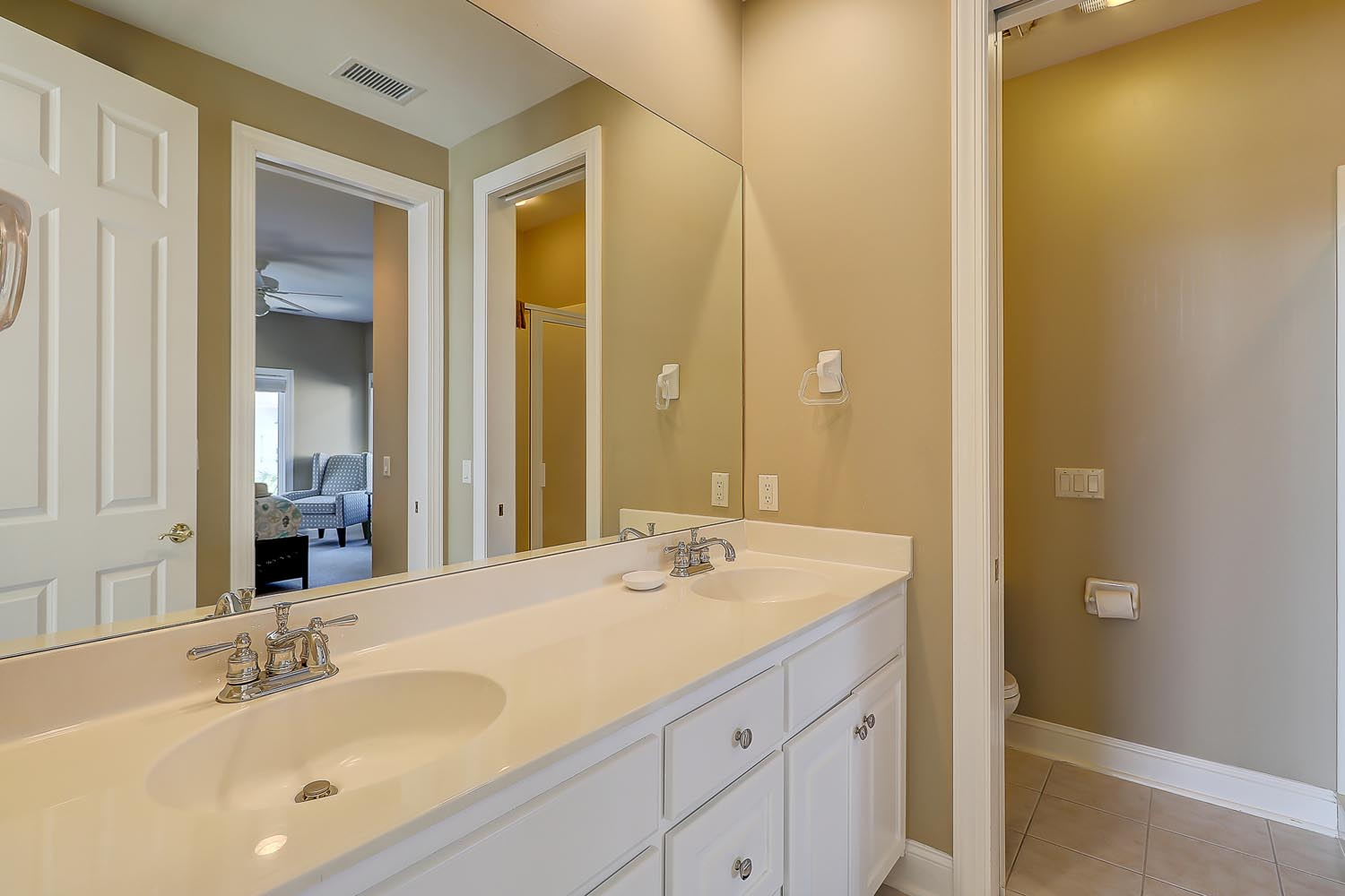 Upstairs hall bathroom with dual vanities, water closet and stand up shower
