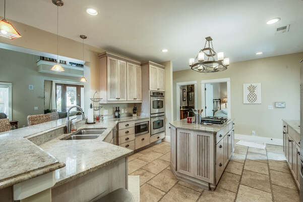The gourmet chefs kitchen features stone counters, custom cabinetry, gas range, two refrigerators, double oven and a breakfast bar with high top seating for 5