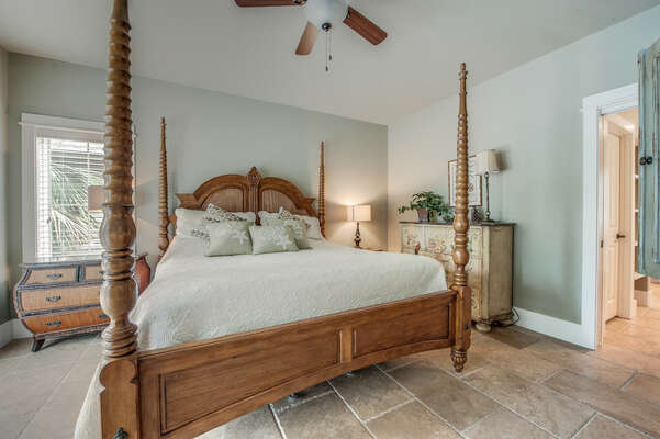 The secondary master bedroom (listed as bedroom 1 in the description) features a king bed, flat panel TV, balcony access, en suite bathroom with clawfoot tub and walk in shower, located on main level just off the dining room and faces the front of the home