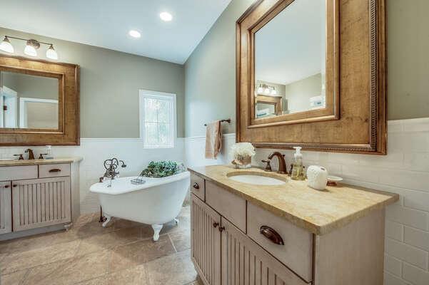 En suite bath in bedroom 1 has dual vanities, clawfoot tub and glass-enclosed walk in shower