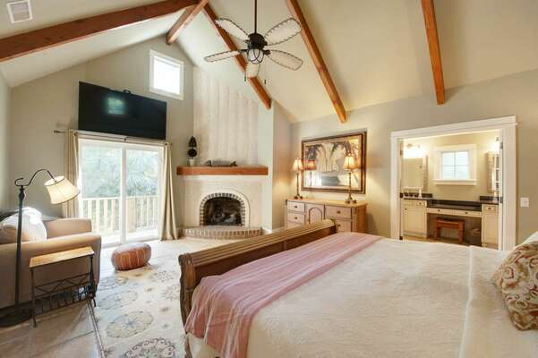 First floor main master suite has king bed, flat panel TV, decorative tabby shell fireplace, sitting area, access to rear balcony and an en suite bath with tub, dual vanities and glass-enclosed walk in shower