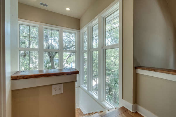 Beautiful stairwell with large windows filtering in natural light through the oak trees