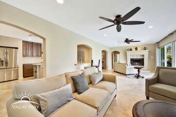 The open living room has a cozy couch, oversize chair and HDTV. Easy access to the kitchen