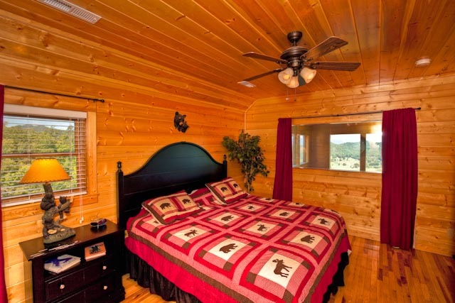 Bedroom with ceiling fan and several windows
