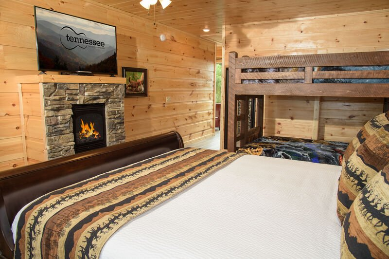 Bedroom with TV, Fireplace, Bunk Beds, and a Larger Bed