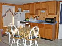 Kitchen area with oak cabinets,refrigerator, stove, and microwave oven.  Table and chairs for four. All dishes and utensils, pots and pans needed to cook a great meal. Lobsta Pot Too.