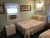 Bedroom with two full beds, air conditioner and ceiling fan.