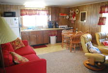 Family Room with 2 Leather recliners with footrests, pull out sofa bed, Dining table with 4 chairs.  Kitchen has double sink, microwave, refrigerator and Full size stove.  Kitchen is fully stocked with plates, bowls, glasses, pans, utensils and Lobster Pot.