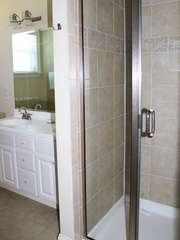 The bathroom features a large tile shower.