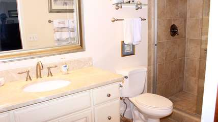 The renovated bath has an extra large vanity and tile flooring.