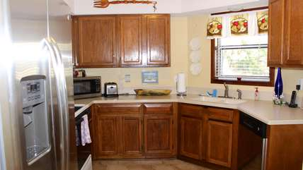 This spacious kitchen has Corian countertops and well stocked cabinets.