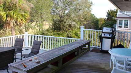 The back deck has a grill and tables for dining.