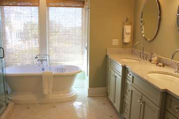 The master bathroom features dual sinks, custom cabinetry, and marble counter tops.