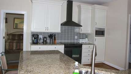 It features granite counters and custom cabinets.