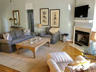 The living room has new furniture and a large HDTV over the fireplace.