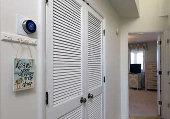 Hall closets include stacked washer and dryer