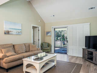 The living room has a  TV for viewing, and sliders leading to the screened porch.