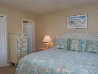 The master bedroom has a king bed. Windows offer views of the golf course.