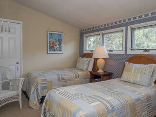 The room features two twin beds, and a balcony overlooking the living area.