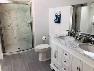 The beautifully remodeled bathroom has a large walk-in shower, dual sink vanity and high ceilings.