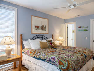 The 2nd master bedroom has a soft blue decor and a king bed.