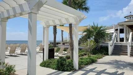 Eye pleasing pergolas frame the beach lounge area leading towards