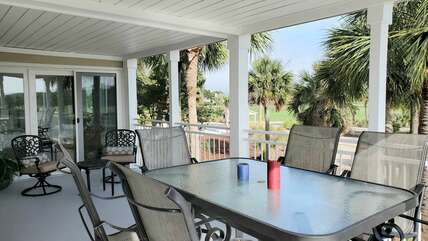 L-shape covered patio; bar-style dining table with 6 swivel stools and separate seating group