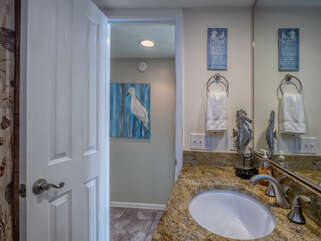 There is a full bath that is accessible from the hall. It has granite counters.