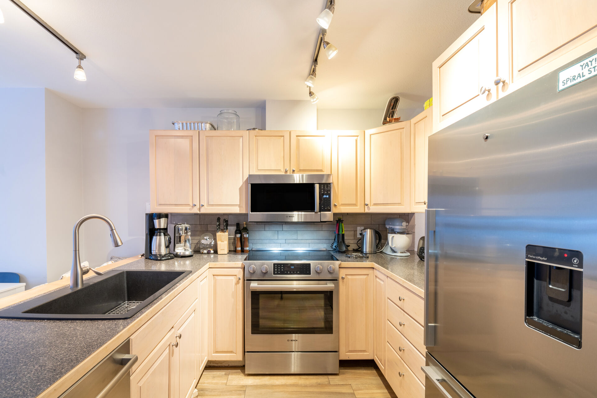 Kitchen with a refrigerator, an oven, microwave and sink