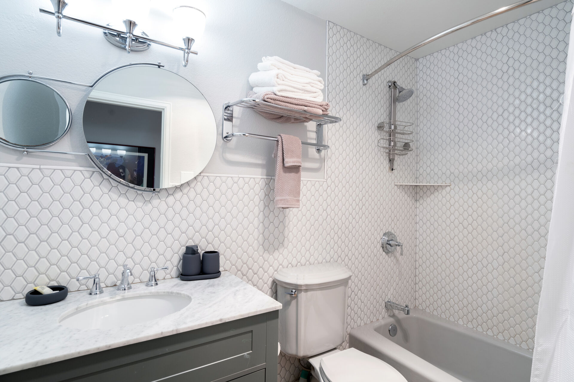 A shower/tub, a sink and towels