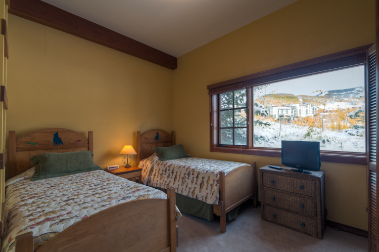 2nd twin bedroom with two single beds and a tv