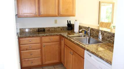 The updated kitchen has granite counters and is well stocked.