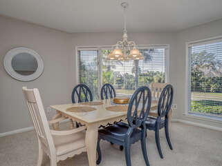 Windows allow sunshine to brighten this living/dining room.