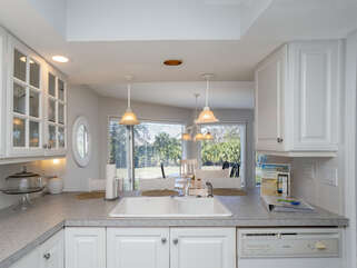 The kitchen has white cabinetry and is spacious.