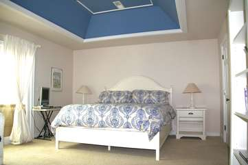 The master bedroom has a king bed, tray ceiling, and access to the sun room.