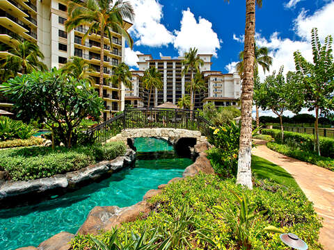One of the Walkways through the Property leading to this Ko Olina beach villas in Hawaii, with a bridge over a river and island landscaping.