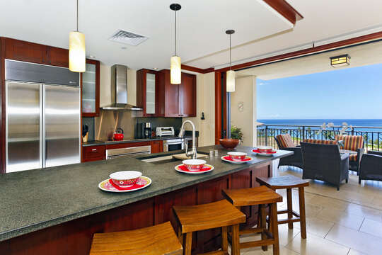 The Kitchen with Island, Stools, Balcony Chairs, and the Ocean View.