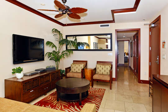 Living Area with TV, Armchairs, Coffee Table, Big Mirror, and Ceiling Fan.