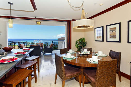 Dining Table, Chairs, Kitchen Island with Stools, and a View of the Ocean from the Balcony.