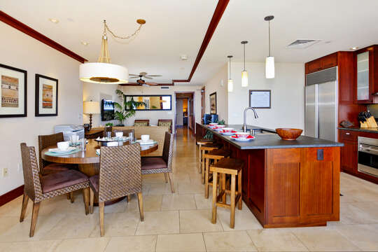 Kitchen with Island, Stools, Dining Table, Chairs, Refrigerator, and Ceiling Lamps.