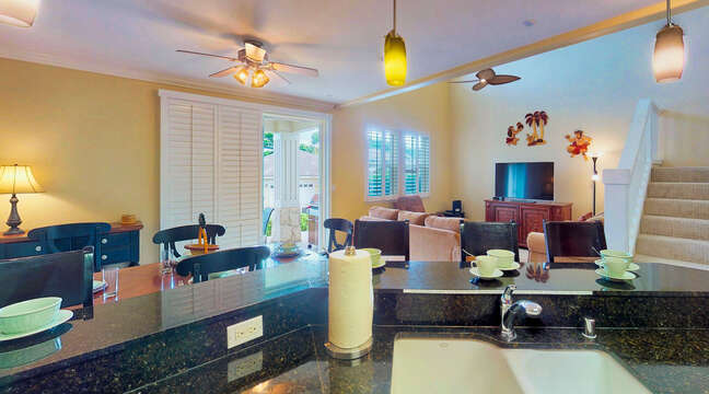 Kitchen Bar, High Chairs, Ceiling Fan, Sofas, TV Stand, TV, and Stairs.