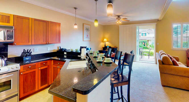 Kitchen with Bar, High Chairs, Sofa, Patio Sliding Doors, and Ceiling Lamps.