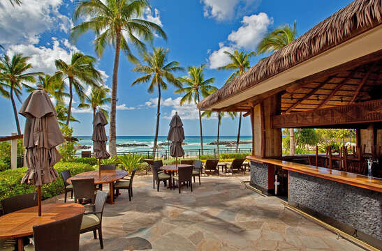 Beach Bar with View of the Ocean, Tables, Chairs, and Table Umbrellas.